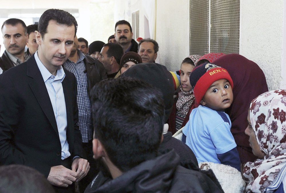 Syria's President Bashar Assad speaks with children during his visit to displaced Syrians in the town of Adra in the countryside outside Damascus on Wednesday.