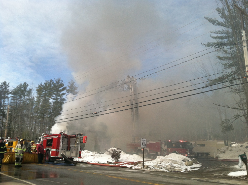 Heavy smoke billows from a house fire on Route 111 iin Arundel on Friday.