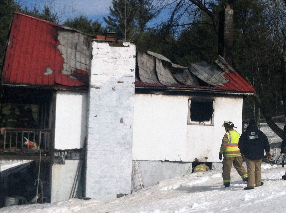Firefighters inspect the scene after a fire destroyed this home at 1077 Hopper Road in Acton on Friday morning.