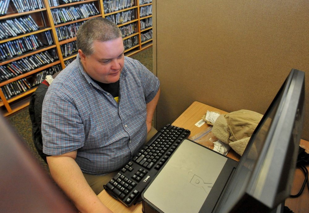 Corey Hewins surfs the Web at the Waterville Public Library on Friday, searching for vacation destinations in California.
