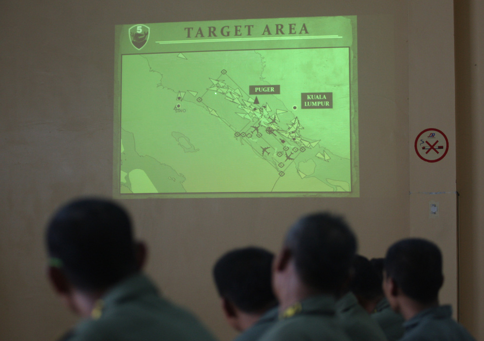 "Indonesian Air Force personnel of the 5th Air Squadron ""Black Mermaids"" listen to a briefing as an operation map is projected on the wall following a search mission for the missing Malaysia Airlines Boeing 777."