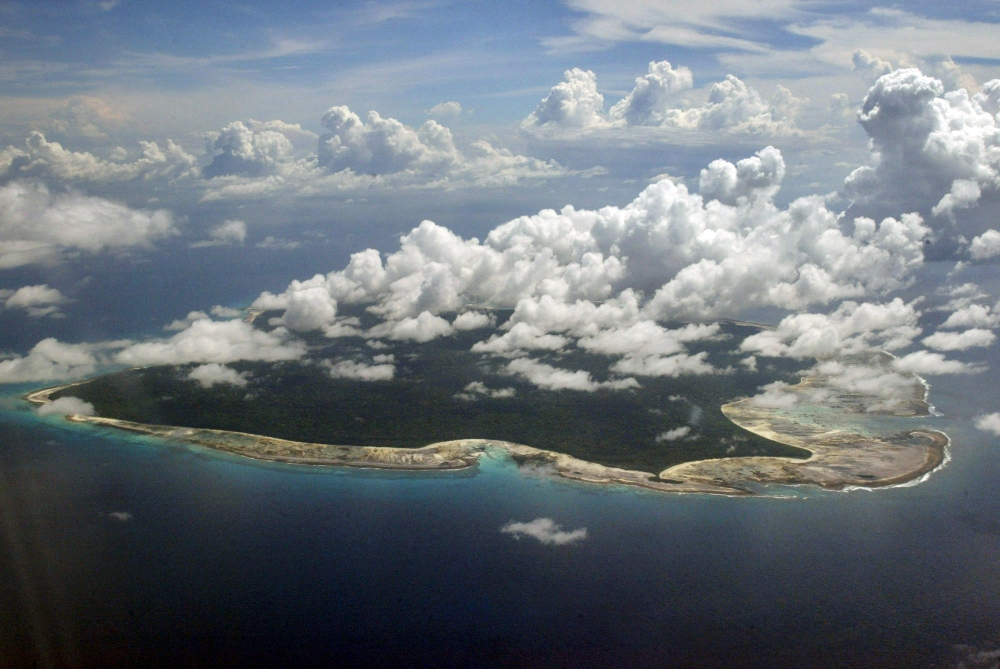 In this 2005 file photo, clouds hang over the North Sentinel Island, in India's southeastern Andaman and Nicobar Islands. India used heat sensors on flights over hundreds of uninhabited Andaman Sea islands Friday, and will expand its search for the missing Malaysia Airlines jet farther west into the Bay of Bengal, officials said.