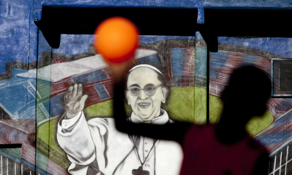 A boy plays soccer in front a mural of Pope Francis at the Villa 1-11-14 slum in Buenos Aires, Argentina. Before he was elected pope, he assigned many priests to parishes in slums around the capital.