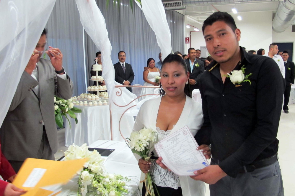 One of 31 couples who married on Valentine's Day at a mass wedding at the Plantronics factory pose as they receive a certificate.