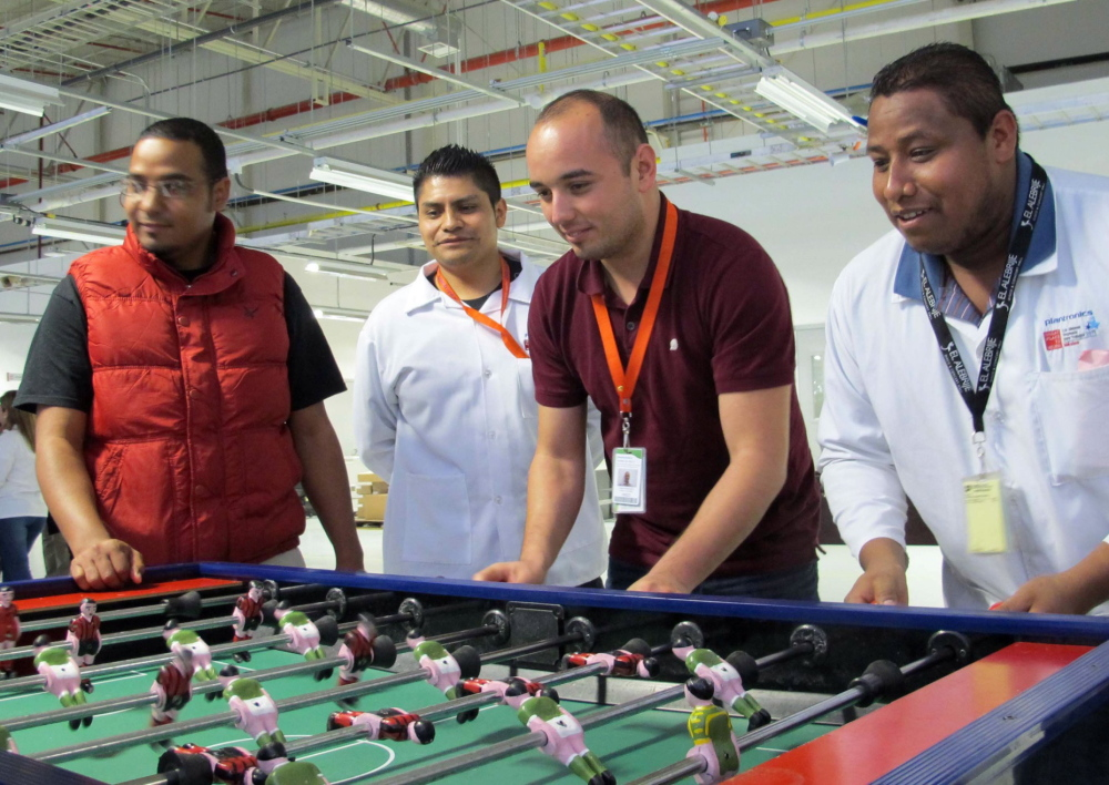 Employees on an afternoon break at the Plantronics headset assembly plant play foosball at tables set apart from assembly lines.