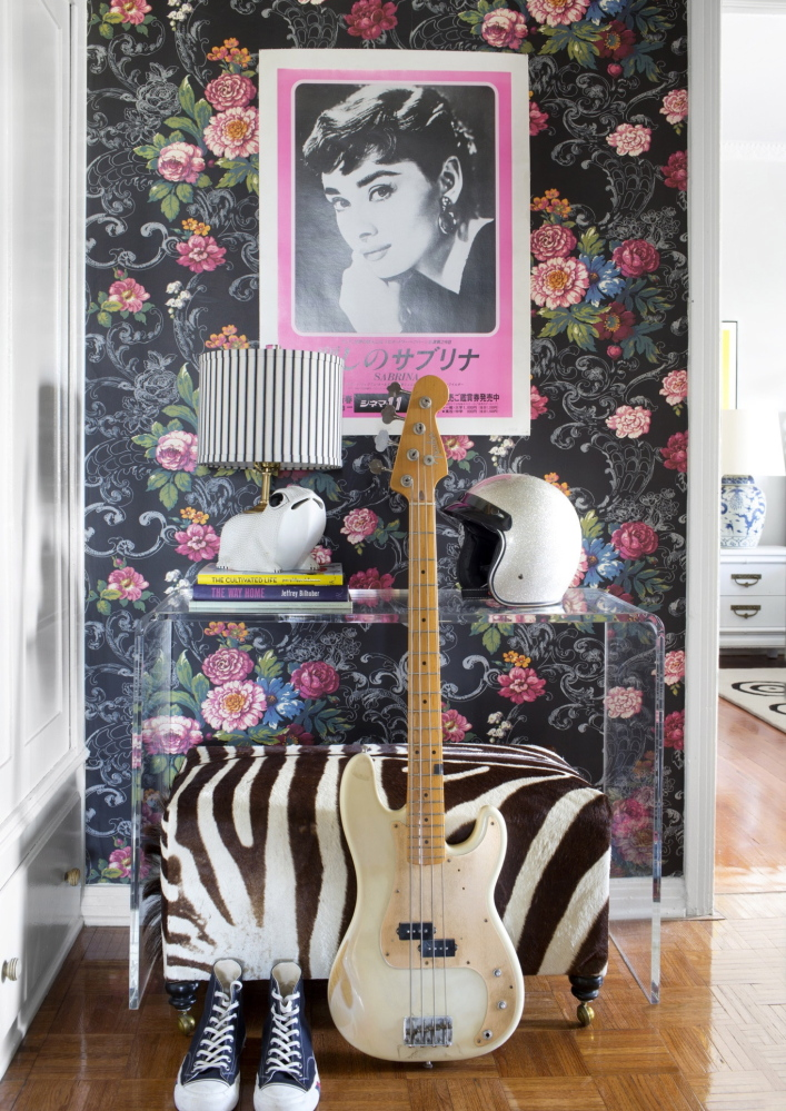 "Floral wallpaper is contrasted with modern furniture and unexpected accessories like a bike helmet and a vintage Japanese poster for the movie ""Sabrina,"" to create a fresh and edgy look."