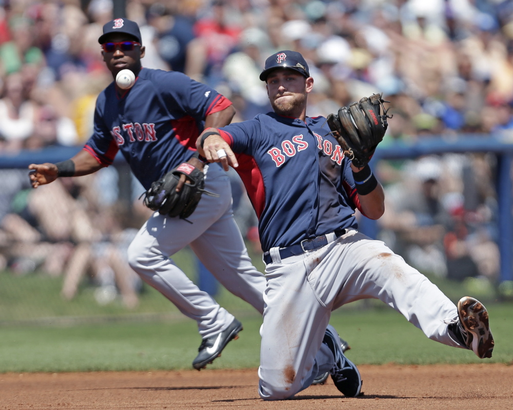 Boston third baseman Will Middlebrooks makes a throw in the first inning of an 8-4 exhibition loss to Tampa Bay at Port Charlotte, Fla., on Sunday. Backing up the play is Boston second baseman Jonathan Herrera.