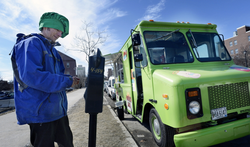 James Dinsmore of Wicked Good Truck feeds the parking meter Monday. The food truck's owner wants Portland's ordinance changed.
