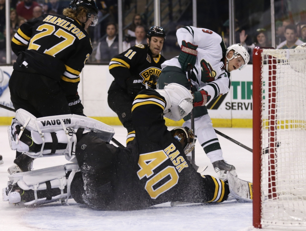 Boston Bruins goalie Tuukka Rask (40) drops to the ice to make a save on a shot by Minnesota Wild center Mikko Koivu (9) during the first period of an NHL hockey game, Monday, March 17, 2014, in Boston. (AP Photo/Charles Krupa)