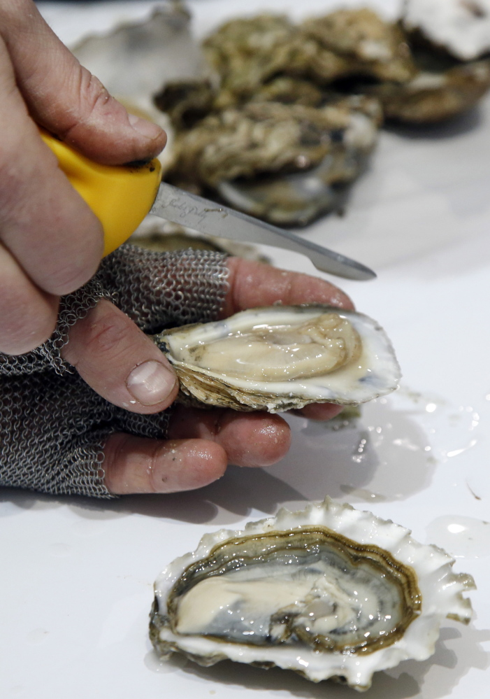 Patrick McMurray, owner of Starfish Oyster Bed & Grill of Toronto, Canada, shows off his oyster shucking skill.
