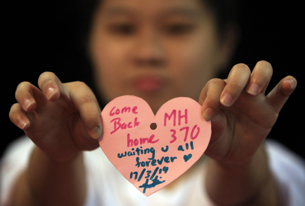 A woman holds a heart-shaped paper with messages for passengers aboard a missing Malaysia Airlines plane, as she poses for a photo during an event in Kuala Lumpur, Malaysia, on Monday.