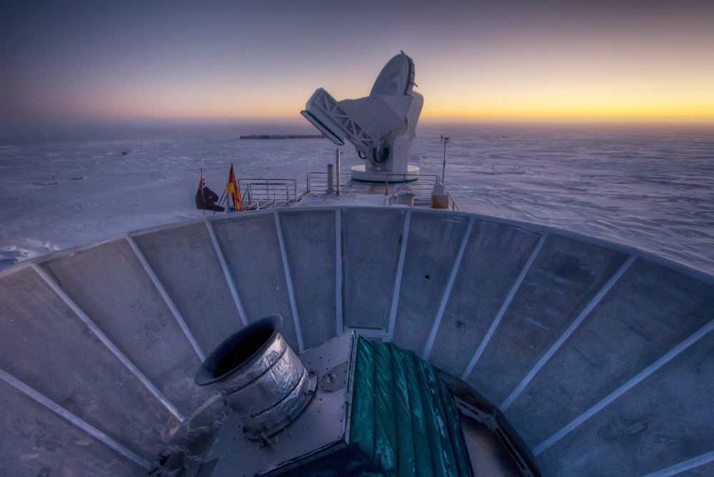"The sun sets behind the BICEP2 telescope, foreground, and the South Pole Telescope in Antarctica. In the faint glowing remains of the Big Bang, scientists found ""smoking gun"" evidence that the universe began with a split-second of astonishingly rapid growth from a seed far smaller than an atom."