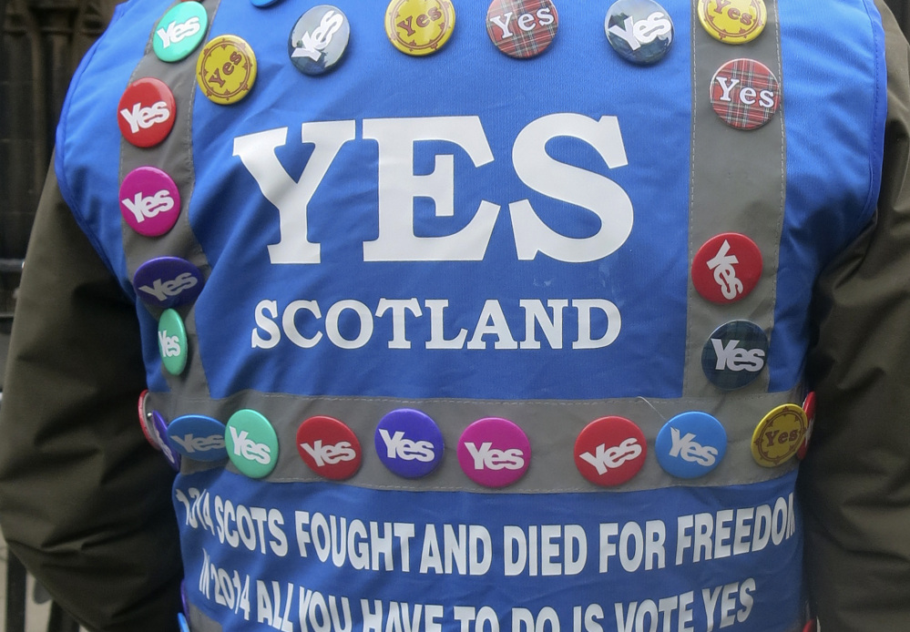 A man wears a multitude of 'yes' campaign badges during a march in Scotland.