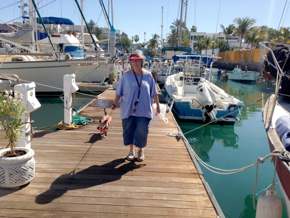 Allyson van Os of Dallas walks on the dock with her dog Pequena. She and her husband, Ed, live on their boat in La Paz, Mexico, from October to June.