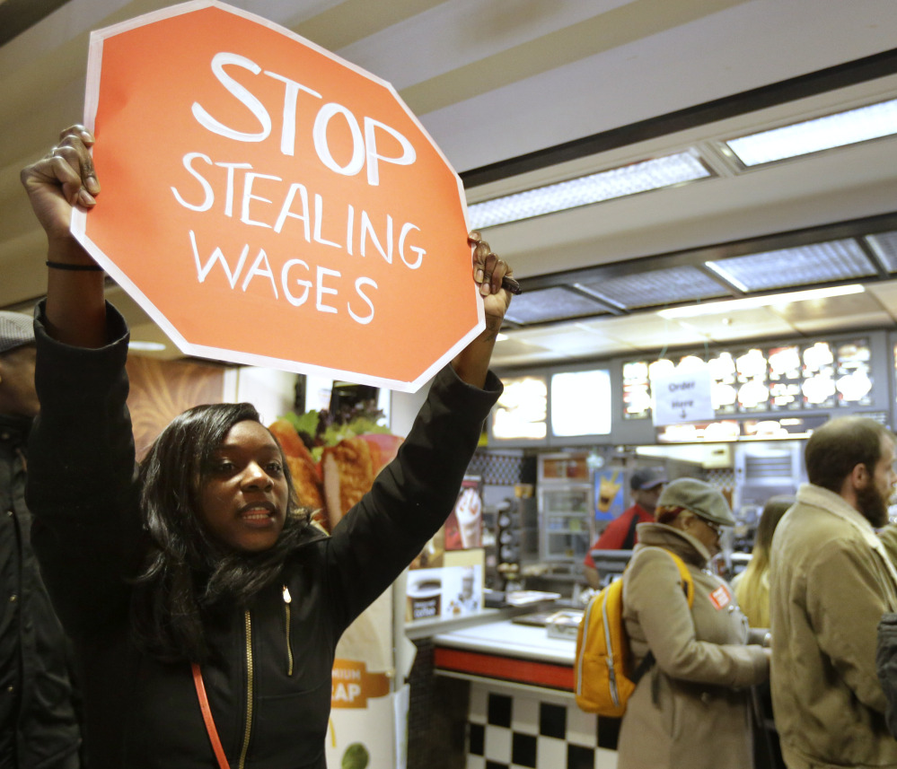 Demonstrator Sherae Speight holds a placard and chants during a protest at a McDonald's restaurant in Boston Tuesday. Protesters wanted to call attention to the denial of overtime pay and other wages workers say the company owes its workers.