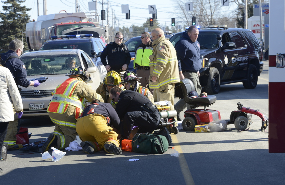 Windham fire and rescue personnel stabilize a man who was hit by a car as he tried to cross Route 302 in his wheelchair in front of a Windham shopping center.