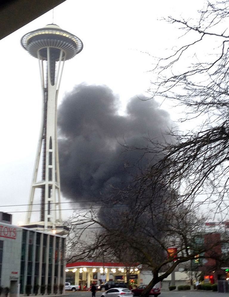 In this photo provided by KIRO- TV, smoke rises at the scene of a helicopter crash outside the KOMO-TV studios near the space needle in Seattle.
