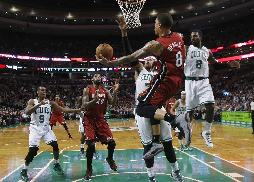 Miami Heat forward Michael Beasley leaps behind the basket to make a play as Boston Celtics center Jared Sullinger (7) and forward Jeff Green (8) defend in the first quarter Wednesday in Boston.