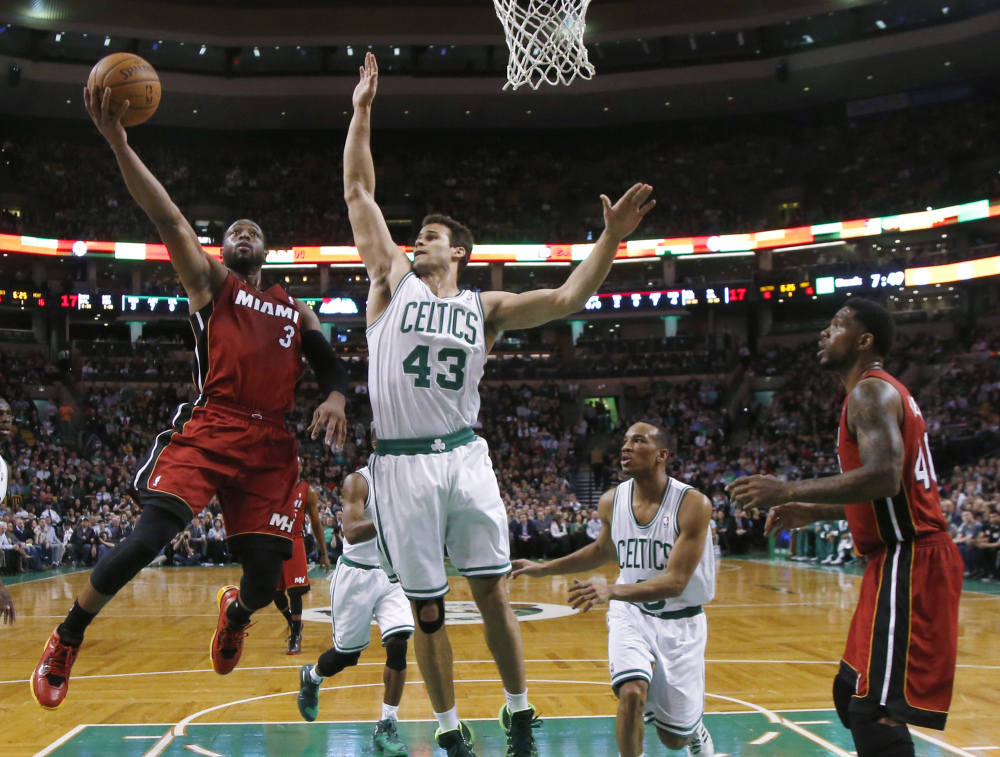 Miami Heat guard Dwyane Wade drives to the basket against Boston Celtics center Kris Humphries in the first quarter Wednesday in Boston.