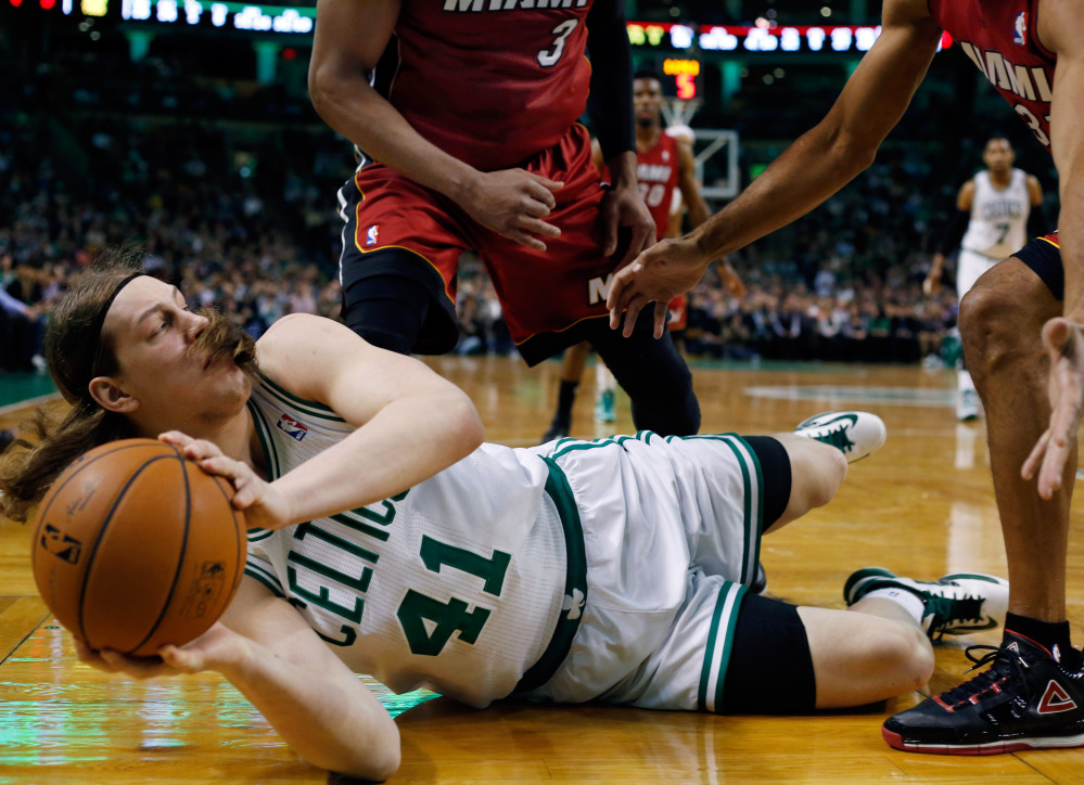 Kelly Olynyk of the Boston Celtics looks to pass from the floor Wednesday night as Miami Heat defenders attempt to trap him. The Celtics came away with a 101-96 victory.