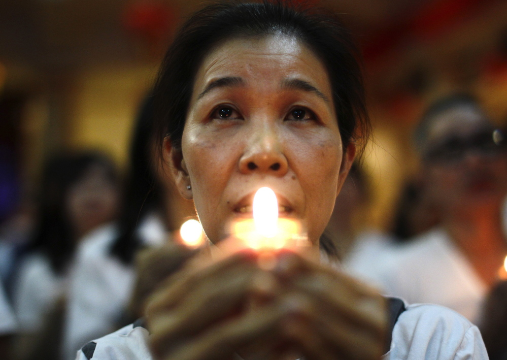 A woman prays in Kuala Lumpur, Malaysia, on Wednesday. Relatives of passengers missing on Malaysia Airlines plane are increasingly distraught.