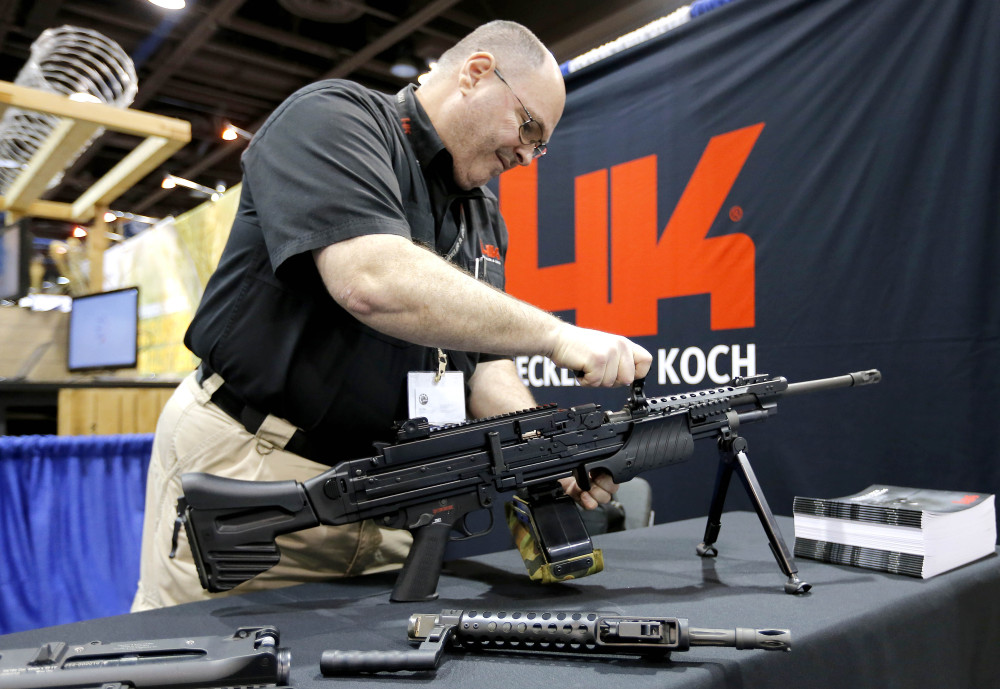 Barry Witt, of Heckler & Koch arms manufacturers, sets up a weapons display at the 8th annual Border Security Expo on Tuesday in Phoenix.