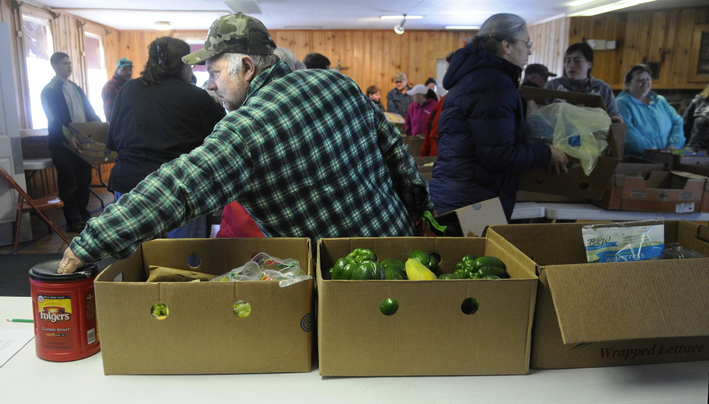 Douglas Mason Sr. of Augusta makes a contribution Tuesday at the East Winthrop Baptist Church Food Ministry before collecting fruit, vegetables and other perishable items that were donated by Hannaford.
