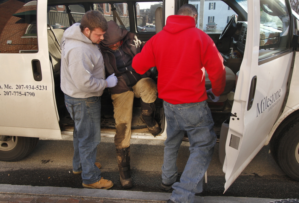 Joe McNally, left, HOME Team coordinator, and outreach worker Allen Patti, right, help Don Dietz get to the Milestone shelter on India Street in Portland on Thursday. Widely considered an effective social safety net, the Homeless Outreach and Mobile Engagement Team has lost its $75,000 grant funding.