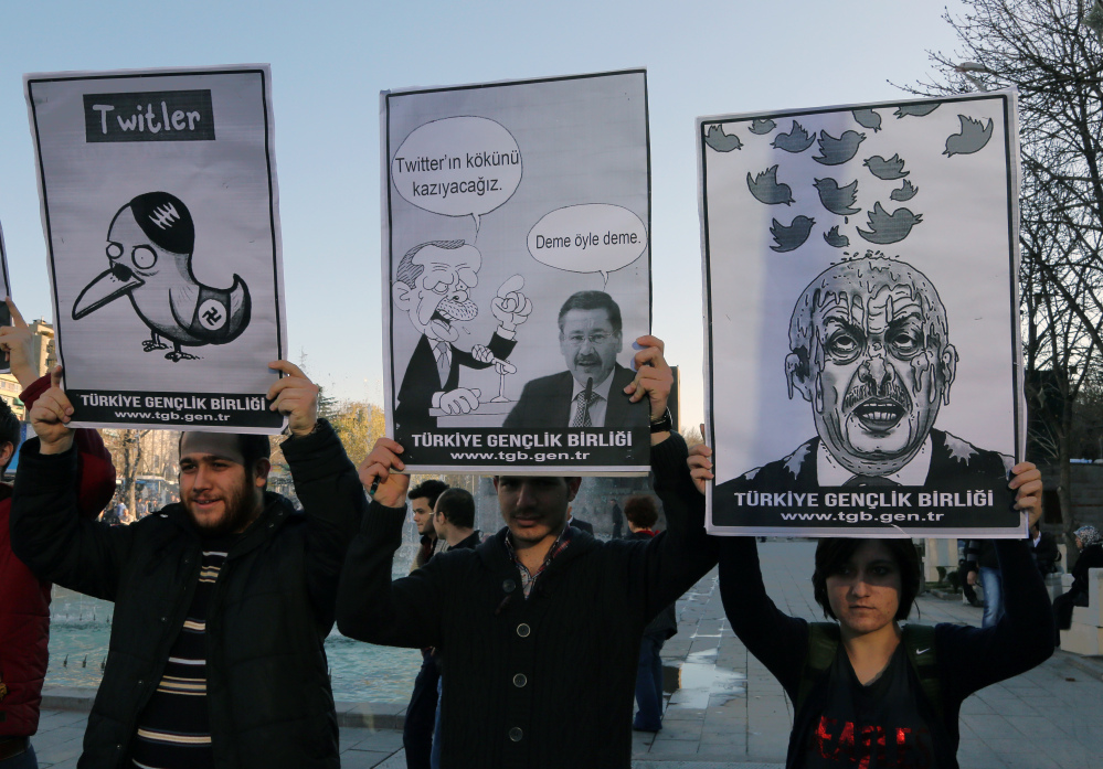 Members of the Turkish Youth Union hold cartoons depicting Prime Minister Recep Tayyip Erdogan during a protest against a ban on Twitter in Ankara, Turkey, on Friday.