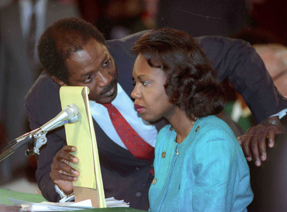 Counsel Charles Ogeltree uses a legal pad to cover a microphone as he advises law professor Anita Hill on Oct. 11, 1991, during hearings on Judge Clarence Thomas.