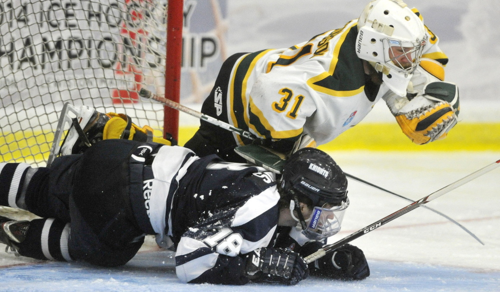 St. Norbert goalie David Jacobson gets taken down by a sliding Stephen Collins of SUNY-Geneseo during St. Norbert's 6-2 victory. The Green Knights pulled away from a 2-2 tie late in the second period.