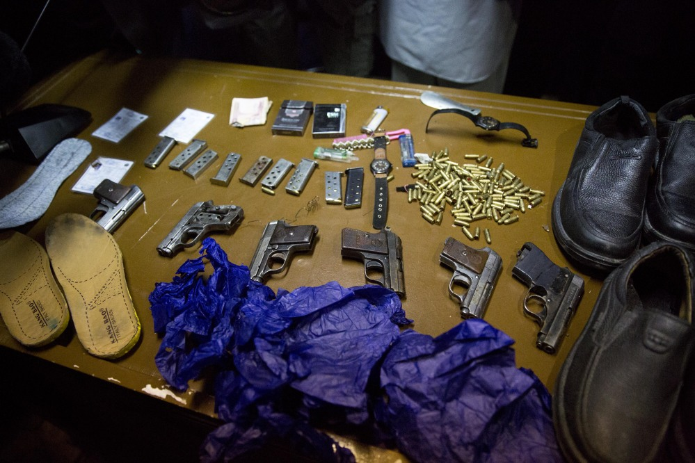 Afghanistan's intelligence service displays some of the weapons and belongings of the men who opened fire Thursday in the Serena Hotel.