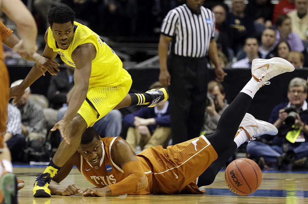 Michigan guard Derrick Walton Jr., left, and Texas forward Jonathan Holmes chase after a loose ball during the second half of a third-round game of the NCAA college basketball tournament Saturday.