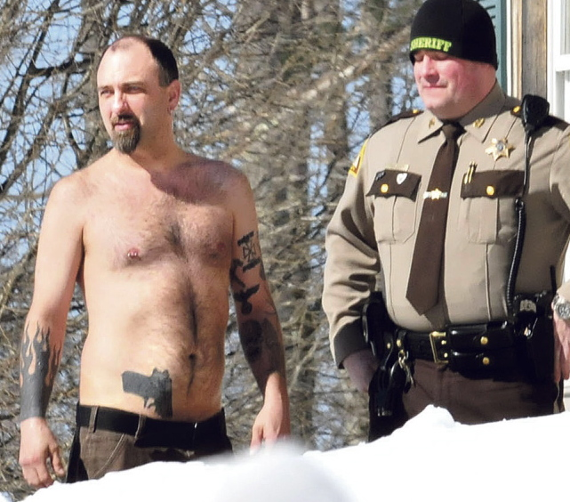 Norridgewock resident Michael Smith stands beside a Somerset County sheriff's deputy after he was coaxed out of his home Tuesday.