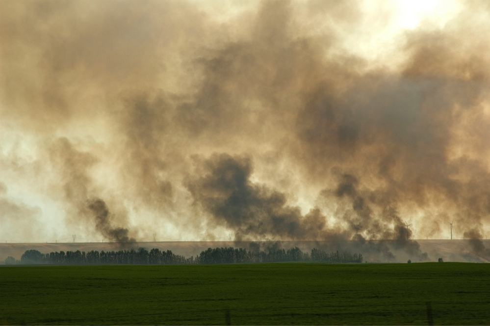 Bouchard's image of a fire behind a large farm's planted field.