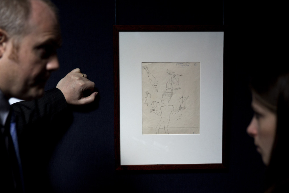 "A Sotheby's employee, left, speaks to a journalist beside an untitled illustration of a boy with six birds by the late Beatles members John Lennon at the auction house's premises in central London. The ink drawing in black with editorial notes is estimated to fetch between $19,795 to $24,744 in a June 4 New York sale of Lennon autograph drawings and manuscripts produced for his books ""In His Own Write"" and ""A Spaniard in the Works""."