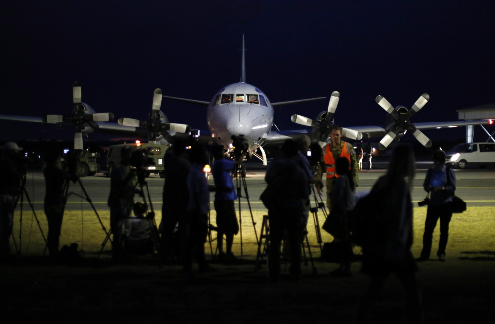International press gather around a Royal Australian Air Force AP-3C Orion upon its return from a search for Malaysian Airlines flight MH370 over the Indian Ocean, at RAAF Base Pearce north of Perth, March 24, 2014. An Australian navy ship was close to finding possible debris from a missing Malaysia Airlines jetliner on Monday as a mounting number of sightings of floating objects raised hopes wreckage of the plane may soon be found. The HMAS Success should reach two objects spotted by Australian military aircraft by Tuesday morning at the latest, Malaysia's government said, offering the first chance of picking up suspected debris from the plane. REUTERS/Jason Reed (AUSTRALIA - Tags: MILITARY TRANSPORT DISASTER MEDIA) - RTR3IC1H