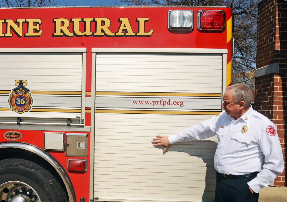 Fire Chief Hank Clemmensen of Palatine, Ill., shows where ads will appear on the sides of firetrucks.