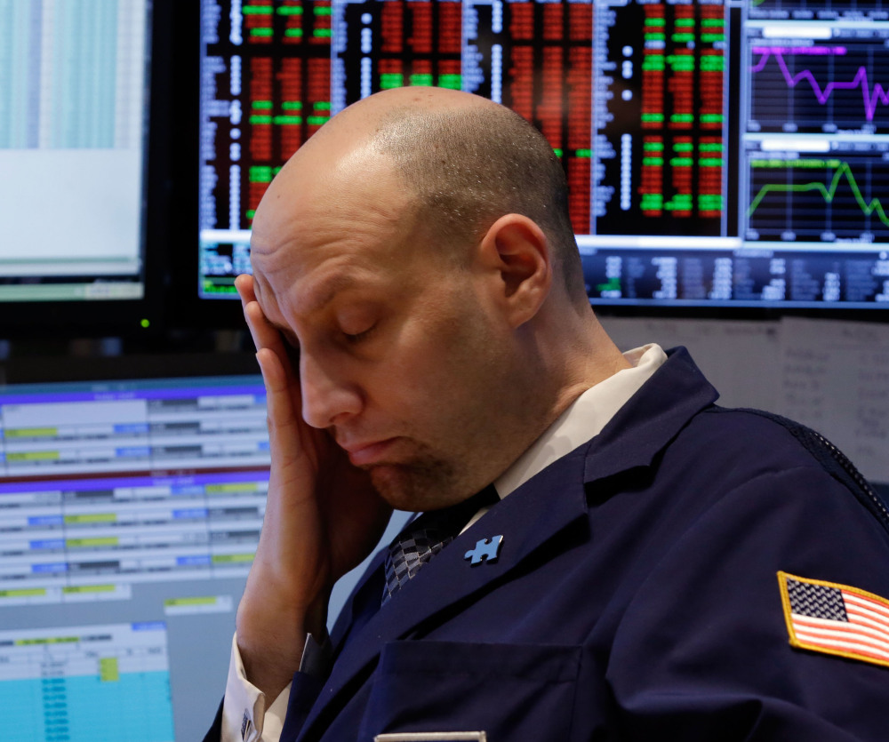 Specialist Meric Greenbaum works at his post last week on the floor of the New York Stock Exchange. U.S. stocks fell Monday as tensions with Russia escalated.