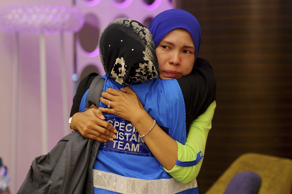 A family member, right, of passengers aboard a missing Malaysia Airlines plane is embraced by a member of Special Assistance Team at a hotel in Putrajaya, Malaysia, Tuesday, March 25, 2014. Malaysia said Tuesday that it has narrowed the search for a downed jetliner to an area the size of Texas and Oklahoma in the southern Indian Ocean, while Australia said improved weather would allow the hunt for possible debris from the plane to resume.
