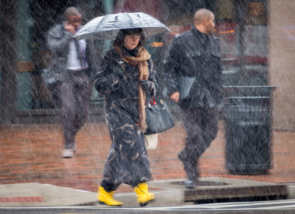 Early-morning commuters walk through snow flurries in Washington on Tuesday.