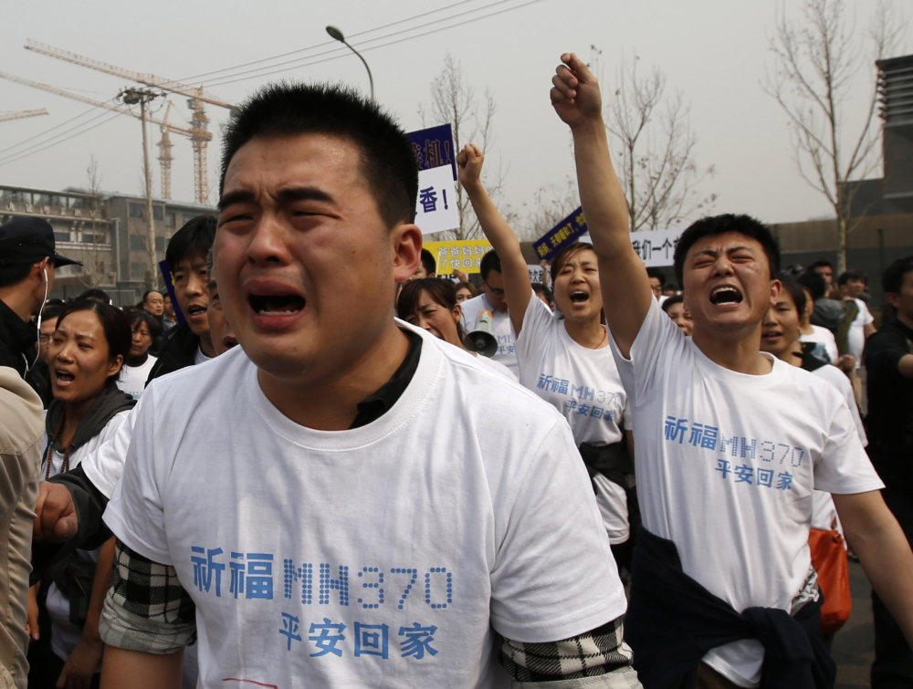 "Family members of passengers on Malaysia Airlines Flight 370 cry as they shout slogans during a protest in front of the Malaysian embassy in Beijing on Tuesday. Relatives of passengers accused the Southeast Asian country of ""delays and deception."""