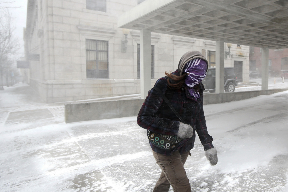 A woman fights through wind-driven snow as she crosses a street during a spring snowstorm in downtown New Bedford, Mass., on Wednesday.