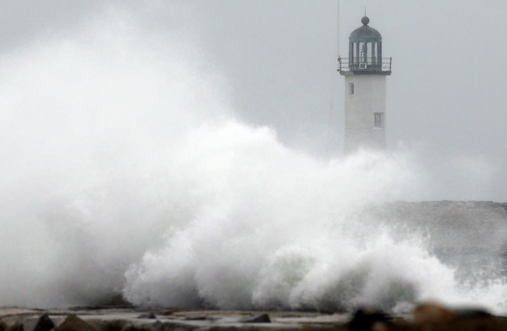 Wind-driven waves crash on a sea wall in front of Scituate Lighthouse in Scituate, Mass., on Wednesday.