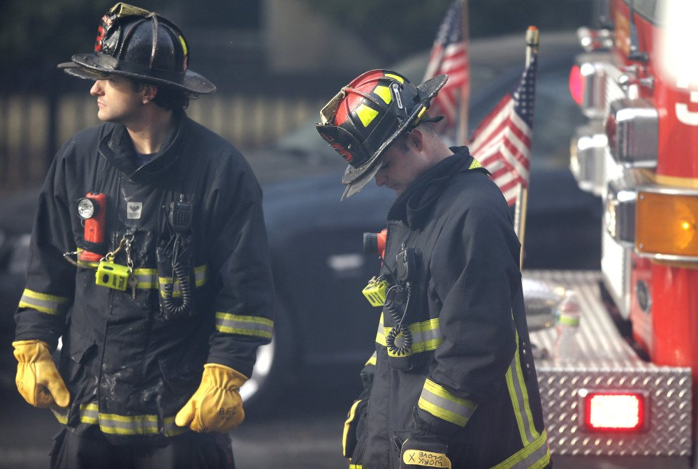 A firefighter, right, lowers his head at the scene of the fire.