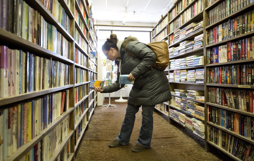 Jen Legere, of Windham, browses through the selection at Annie's Book Stop in Portland on Wednesday. The store, which is closing Saturday after 30 years, is selling its inventory at half-price though Friday.