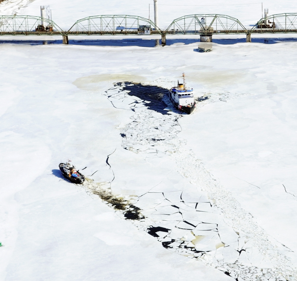 The 65-foot U.S. Coast Guard cutter Bridle, left, and the 140-foot Thunder Bay turn around Thursday near the Richmond-Dresden Bridge on the Kennebec River. They started breaking ice in Bath in the morning.
