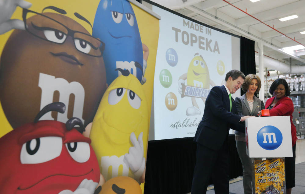 Kansas Gov. Sam Brownback, left, Victoria Mars and Debra Sandler, right, push a button that starts production at the Mars Chocolate North America Topeka Plant on Thursday. Victoria Mars is chairman of the board of Mars Inc., and Sandler is president of Mars Chocolate North America.