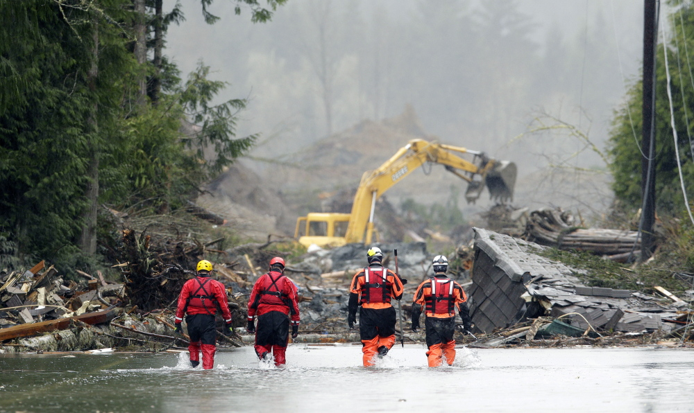 Four search and rescue workers wade through water covering Washington Highway 530 Thursday on the eastern edge of the massive mudslide that struck Saturday near Darrington, Wash. Heavy equipment moves trees and other debris in the background.