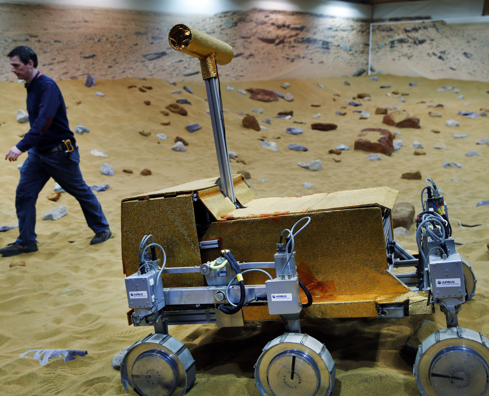 """An engineer walks past a robotic vehicle on the """"Mars Yard"""" testing ground for the European Space Agency's ExoMars program in Stevenage, England."""